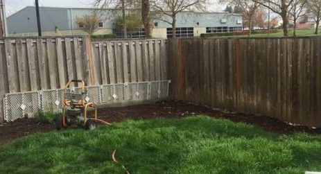 Image of a fence before getting pressure washed